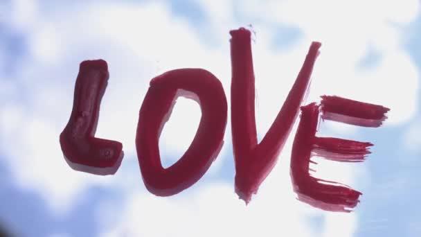 Slovo LOVE ručně napsané na zrcadle s červenou barvou, odraz modré a zamračené oblohy, krásné změny světla, časový odstup ,