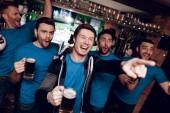 Gruppe von Fußballfans schaut sich Spiel an und trinkt abends Bier in Sportbar