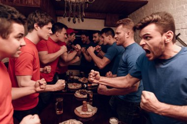 Red and blue teams of hooligan fans fighting at sports bar while watching football game