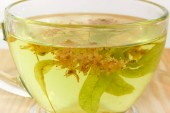 Fragment of the transparent glass cup with linden flower tea closeup at selective focus