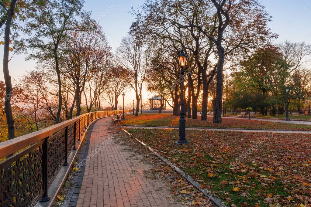 Alley covered with fallen leaves with cast fence, benches, street lights and summer house on a background in the beams of the rising sun in autumn