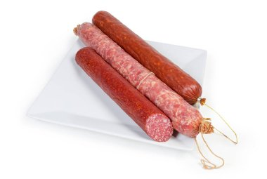Partly cut salami, whole smoked and dry smoked sausages on big white square dish on a white background
