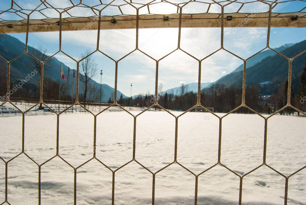 Goal net of a soccer field with snow and panorama on the mountains