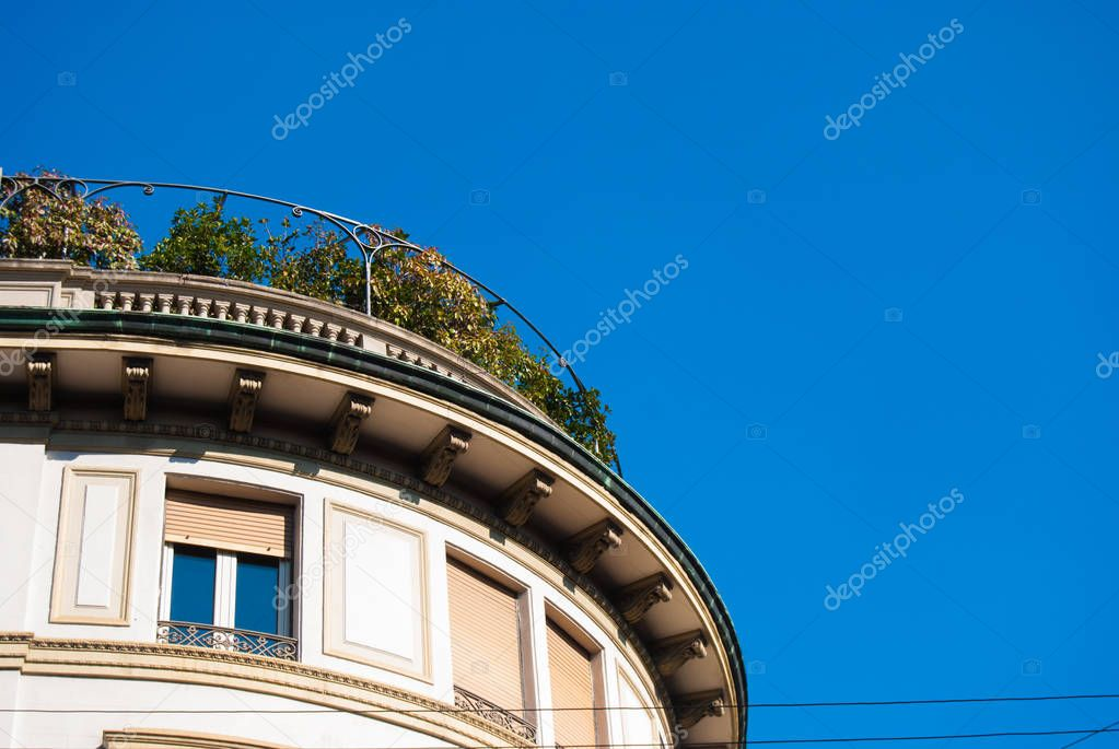 Semicircular urban construction with terrace on the top and a clear blue sky