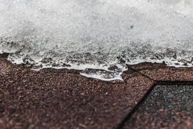 A horizontal texture of snowdrift of white snow with ice and bokeh light on a brown shingles roof in winter