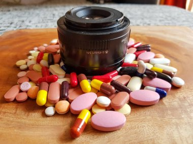 pile of medicine pills tablets capsules around lens in wooden background