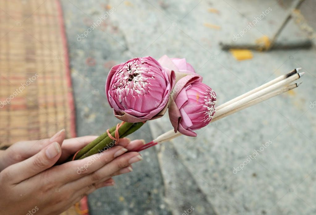 Hand holding lotus flower, candle and incense sticks to pay respect