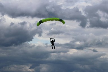 Yaslo, Poland - july 1 2018: The parachutist jumps with the parachute in difficult meteorological conditions. A shaving flight on a parachute wing in the midst of a cloudy dark sky. Flying means