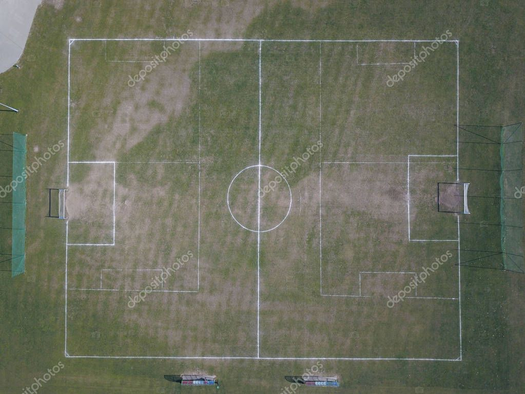 Marking a green artificial football field with a grass cover in the city stadium. The place for conducting competitions and sporting events. Landscape design of a sports. View of drone or aircraft
