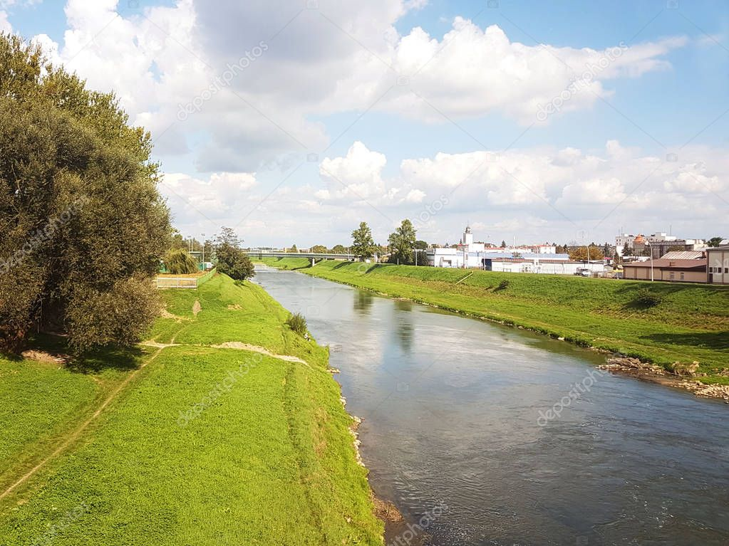 Rzeszow, Poland: city promenade. Wislock river on a summer sunny day. Park for walking citizens with a racetrack. Walk outdoors. Water artery of the settlement. Rest and relaxation area.