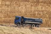 Fotografie Ein schwerer, vierachsiger Muldenkipper mit blauer Ladung fährt auf einem Feldweg vor dem Hintergrund einer Lehmböschung. Karriere und Straßenbau. Fahrerberuf. Transport von Materialien für die Landschaft