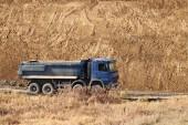 Fotografie Ein schwerer, vierachsiger Muldenkipper mit blauer Ladung fährt auf einem Feldweg vor dem Hintergrund einer Lehmböschung. Karriere und Straßenbau. Fahrerberuf. Transport von Materialien für die Landschaft.