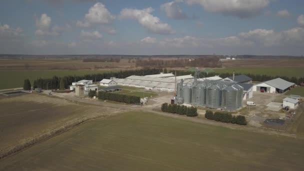 A kilátás a magassága egy nagy farm, zöld dombos mezők között található. Videó a drone vagy a quadro. Agro-ipari komplexum rozsdamentes acél Siló. Az ökológiai élelmiszerek előállítása. Tejelő ipar