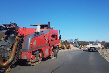 Laying asphalt with the help of heavy special equipment. The construction of the road. Modern technologies laying highway with a solid surface. People work at a construction site. Rolling asphalt