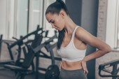Atletická kráska s bolesti zad po cvičení v posilovně. Atraktivní fitness žena s zpět nebo páteře zranění. Sportovkyně třením zádech, po únavné, cvičení. Zranění, úlevu koncepce
