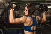 Sportovní životní styl. Zpětná záběr mladého fit a tónovaný zdravá mladá žena cvičit s činkami v posilovně svalové síly silné zvedací kulturistika cvičení výcvik sportovní fitness koncept
