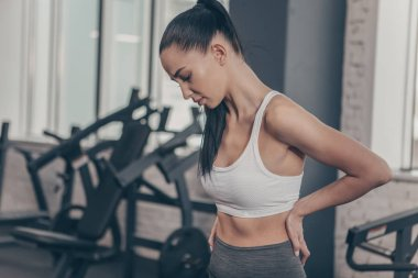 Beautiful athletic woman having backache after workout at the gym. Attractive fitness female having back or spine injury. Sportswoman rubbing her back, after tiring exercising. Injury, relief concept