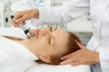 Close up shot of a professional cosmetologist performing stimulating facial treatment for her female client. Beautiful woman getting microcurrent facials at spa salon skincare electrodes apparatus