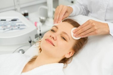 Happy young beautiful woman smiling joyfully while professional beautician cleansing her face with cotton pads preparing for facials at the beauty spa salon clinical cosmetology dermatology skincare
