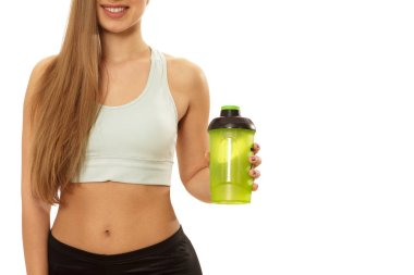 Cropped shot of a young happy beautiful woman with fit and toned perfect body smiling holding bottle of water isolated copy space. Cheerful fitnesswoman after working out. Dieting, hydration concept