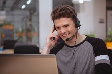 Friendly customer support operator with headset working at call