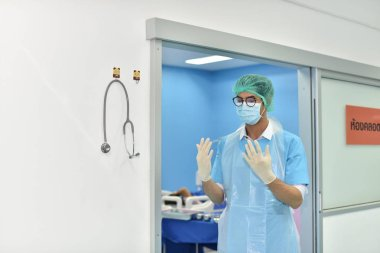 Team surgeon at work in operating room. Surgical light in the operating room. Preparation for the beginning of surgical operation with a cut. The surgeon is performing surgery on the patient.