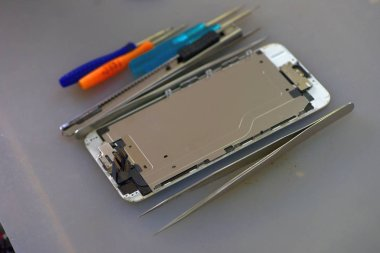 Tools and equipment for repairing and unpacking mobile phones.technician repairing broken mobile phone close-upClose-up Of A Human Hand Repairing Smartphone With ScrewdriverInternal circuits and structural elements of mobile phones