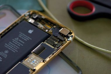 Close-up Of A Human Hand Repairing Smartphone With Screwdriver.Internal circuits and structural elements of mobile phones.Repairing mobile phones and tablets by skilled technicians.Experienced testers and check mobile phones. Before and After Repair