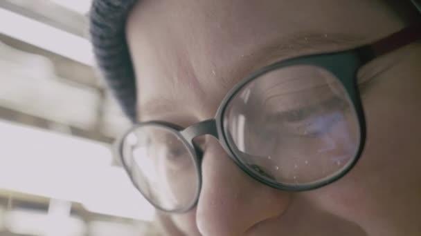 Zár-megjelöl szemcsésedik-ból nő szem szemüveg tükrözi egy működő smartphone képernyő.