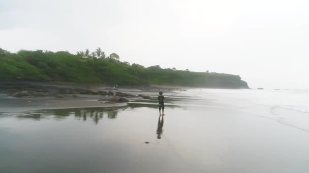 Egy halász fogott halat egy profi pálcával a kezében a partról aranyló napkeltekor. Férfi halászat a strandon naplementében