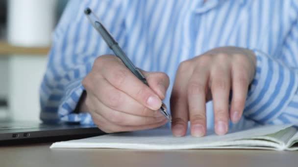 Egy nő kézírása egy jegyzetfüzetbe, ahogy otthon ül az asztalnál a konyhában.