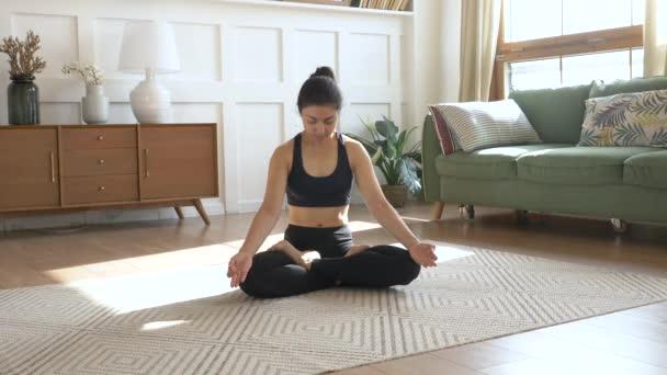 Mladá žena se protahuje doma v obýváku. Mladá indická žena meditující sedí na koberci a dělá strečink dělá jógu