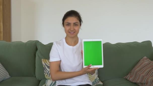 Junges indisches Mädchen lächelt in die Kamera, die auf der Couch sitzt und ein Tablet mit grünem Bildschirm hält, das eine neue App zeigt. Helles und gemütliches Zimmer zu Hause. Home Bildung Lernen zu wissen und zu finanzieren