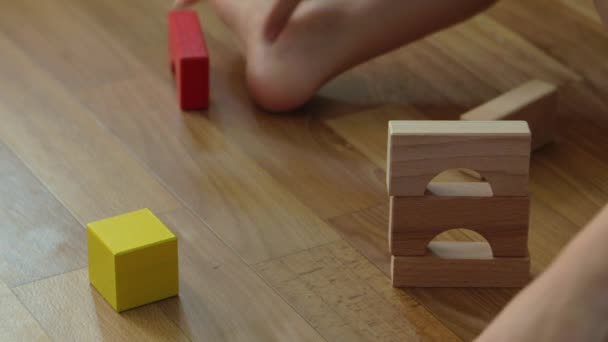3 years old child boy play with wooden blocks, build house at home.