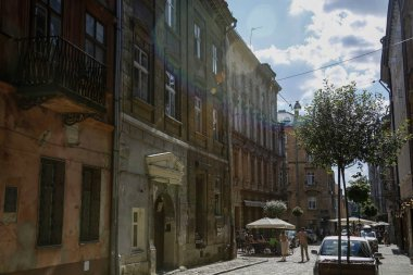 Lviv, Ukraine - june 1, 2019: tourists walking at one of the charming street with cafes in Lviv. Photo taken under the sun with colorful lens flares