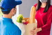 Asijské mladé dodávky muž v uniformě nosit ochrannou masku obličeje on dělat potraviny služby dávat čerstvé jídlo pro ženy zákazník obdrží přední dům pod pandemie coronavirus, Zpět na nový normální koncept