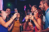 Group of friends dancing and drinking champagne at nightclub party - Happy young people having fun celebrating together in disco club - Entertainment, nightlife and youth lifestyle
