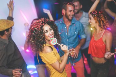 Group of friends dancing and drinking champagne at nightclub - Young happy people having fun and enjoying party eating candy lollipops - Youth friendship lifestyle concept