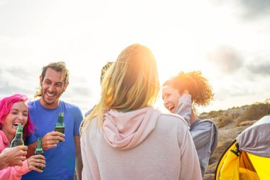 Happy friends drinking beers and having fun camping with tent outdoor - Group of young people enjoying and laughing together in vacation - Travel and youth holidays lifestyle concept