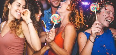 Happy friends doing party dancing in the nightclub - Trendy young people having fun  celebrating together with confetti and candy lollipops in disco - Entertainment, youth lifestyle holidays concept