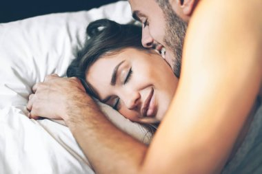 Happy romantic couple having a tender moment in the bed - Young passionate lover waking up in the morning - Man kissing his girlfriend in the bedroom - Love and relationship concept