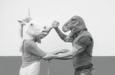 Crazy couple dancing and wearing dinosaur and unicorn mask - Senior trendy people having fun masked at carnival parade - Absurd, eccentric, surreal, fest and funny masquerade concept