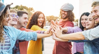 Young friends stacking hands outdoor - Happy millennial people having fun joining and celebrating together - Friendship, empowering, teamwork, partnership and youth lifestyle concept