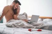 Šťastný pár sledování na počítači když ležel na posteli pod dekou - mladý milenec sleduje roli hry sex video na notebook - lidé, sexuální, intimní, mládež a technologie