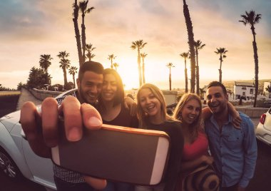 Happy friends standing in front of convertible car and taking selfie with mobile phone camera - Young millennial people having fun on roadtrip in tropical destination - Travel and technology concept