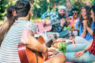 Young people doing picnic and playing guitar in park - Group of