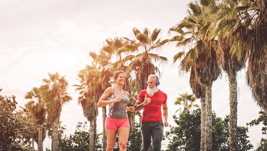 Happy fitness friends running at sunset outdoor - Couple of joggers training at evening time - People jogging, healthy, fit and sport lifestyle concept
