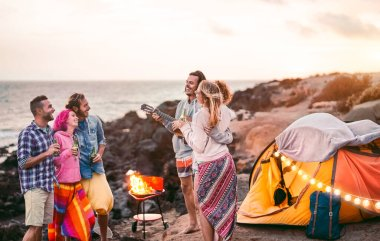 Group happy friends having fun camping outdoor - Young people drinking beers and playing guitar in campsite next the beach - Youth culture and travel vacation concept