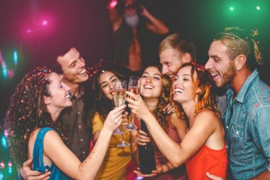 Happy friends celebrating new year eve holidays in disco club - Young people doing private party with deejay and drinking champagne - Youth culture entertainment lifestyle concept