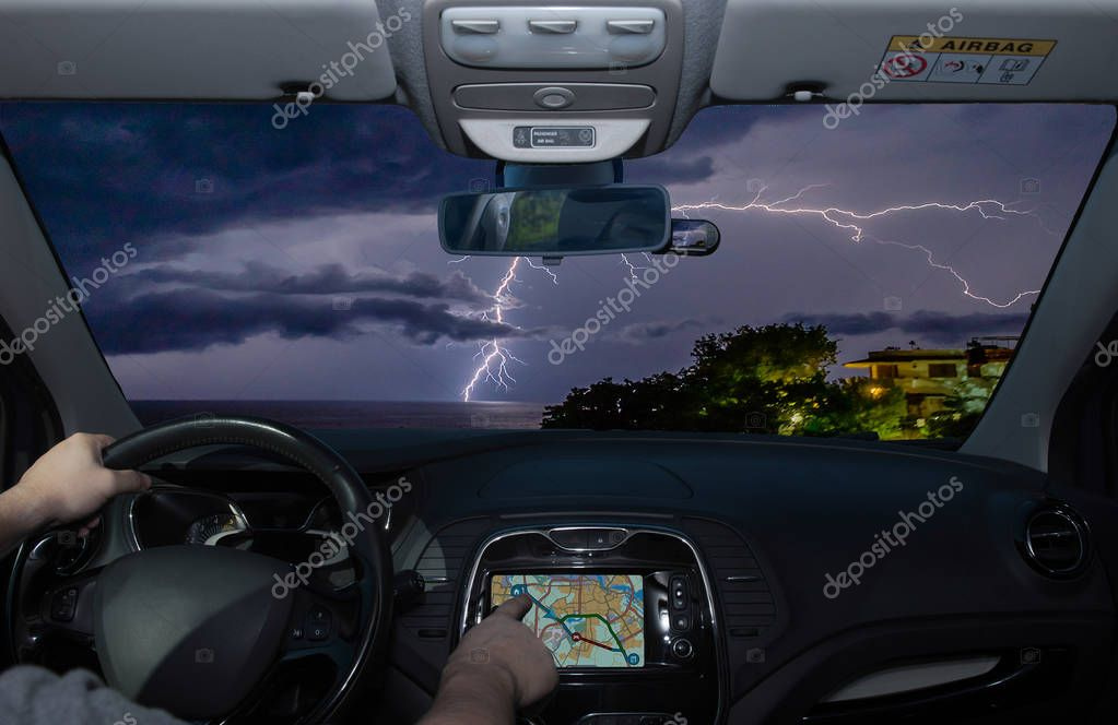 Driving a car while using the touch screen of a GPS navigation system towards lightning over the sea